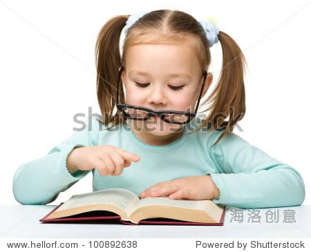 可爱小女孩戴眼镜看书,孤立在白色的