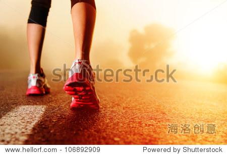 运动员跑步鞋上脚上道路行驶的特写镜头.日出妇女健身