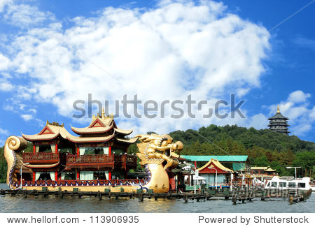 Oriental Dragon boat and Leifeng Pagoda on famous Xihu West Lake with blue sky, Hangzhou, China