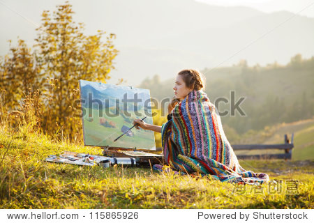 年轻的艺术家绘画一个秋天的风景