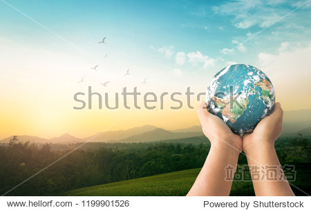 World environment day concept: Human hands holding earth global over mountain sunrise background. Elements of this image furnished by NASA