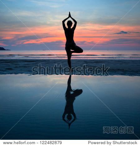 年輕女人練習瑜伽在海岸,夕陽反射在水中圖片