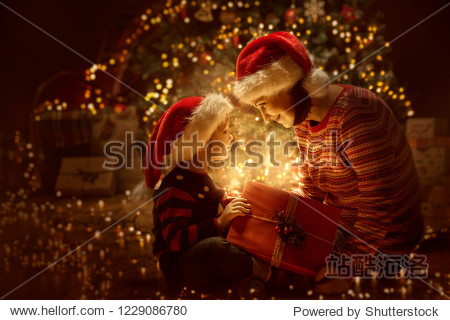 Family open Christmas Lighting Present Gift Box front of Xmas Tree  Happy Mother with Baby Child in Magic Night