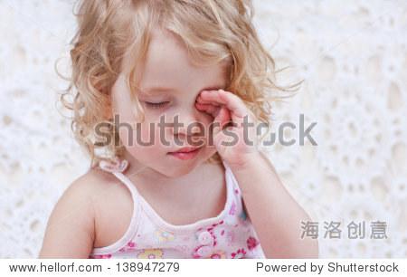 可爱的小女孩的手揉眼睛