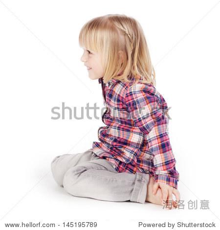 侧面的可爱女孩坐在孤立在白色背景