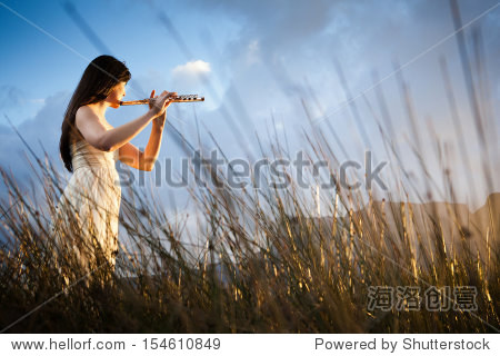 attractive flute player in long grass