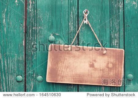着绳子的木制招牌挂在木板的背景