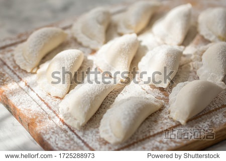 Raw dumplings on a wooden board on grey table in the morning sun. The process of making dumplings. Traditional homemade food.  Slavic traditional dish. Dough for dumplings. Close up. Top view