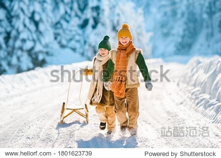 Two little kids have fun in the beautiful winter nature with snow-covered trees. Children walk along a snowy road pulling a sled. Winter knitted wool retro clothes.