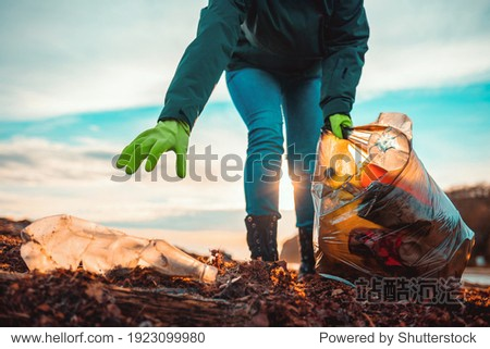 A volunteer collects garbage on a muddy beach. Close-up. The concept of Earth Day. Bottom view.