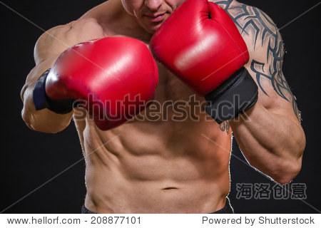 一个纹身的人在红色的拳击手套.男子拳击在黑色背景.