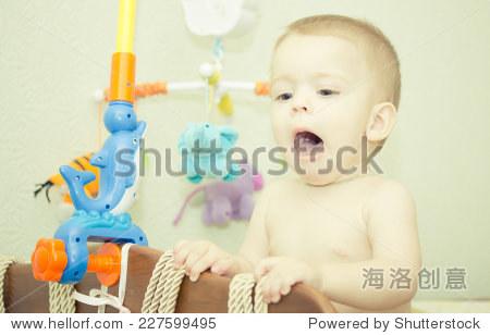 宝宝可爱的笑脸站在床.