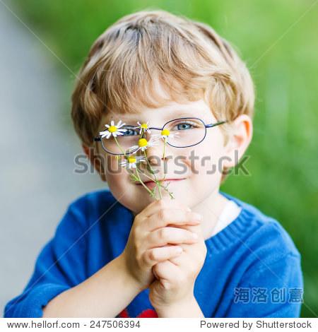 滑稽可爱的孩子戴眼镜的男孩高兴地走在温暖和阳光明媚的夏日.