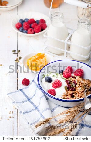 honey, yogurt and fresh berries in a ceramic bowl with a cup of coffee