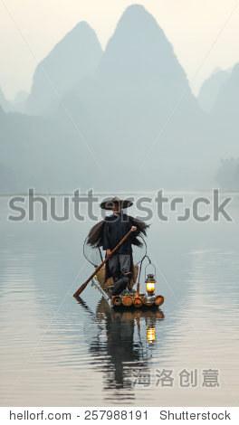 XINGPING, CHINA - OCTOBER 23, 2014: Cormorant fisherman stands on the ancient bamboo boat at morning fog - The Li River, Xingping, China
