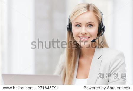 微笑的女性热线接线员耳机和电脑