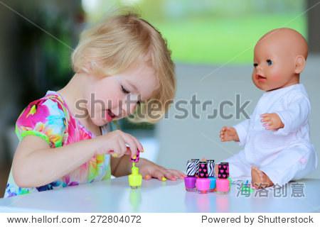 小孩子,可爱的蹒跚学步的女孩在家开心玩彩色指甲油做美甲和画指甲给