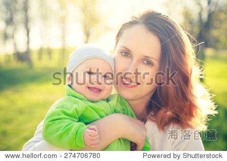 肖像的年轻的母亲带着她微笑的宝宝在公园快乐.春天的