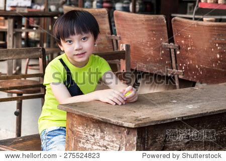asianboynation_little asian boy smiling looking away while on table