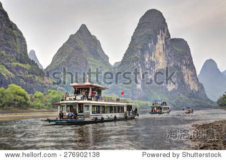 Yangshuo, Guangxi, China - March 29, 2010: Ships carrying tourists move on Lijiang River, countryside of southern China.