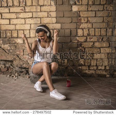 可爱的非洲黑人女孩附近坐了枯燥乏味的黄色砖墙与大白色耳机女性在头