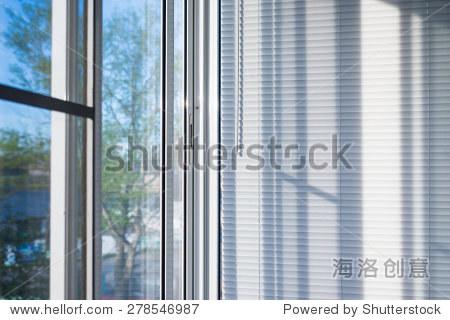 封闭的塑料窗帘在窗户上反射的玻璃