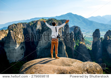 穿着考究的专业摄影师站在山顶附近美丽的风景背景在
