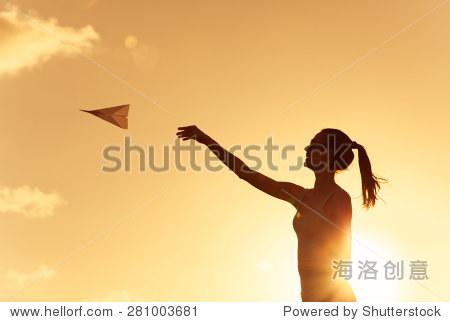 美丽的剪影年轻女子扔纸飞机.