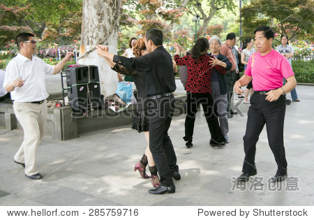 HANGZHOU, CHINA - MAY 3, 2015: Chinese people dancing by the Xihu (West Lake), celebrating their traditions. The West Lake has influenced poets and painters throughout China for its natural beauty.