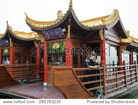 HANGZHOU, CHINA - MAY 3, 2015: Traditional Chinese wooden boat on the Xihu (West Lake. Locals and tourists visit the lake, which has influenced poets and painters throughout China.