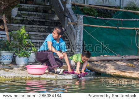 YANGSHUO, CHINA - MAY 01, 2015: A woman and a child washing his clothes next to Yulong river in Yangshuo, China. The Yulong River is a small tributary of the larger Li River.