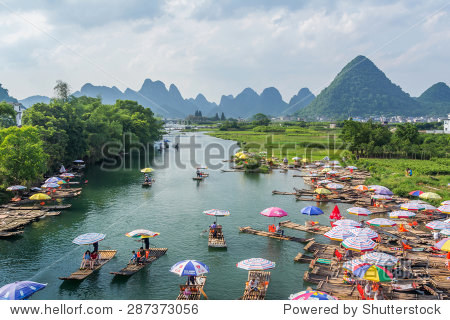 YANGSHUO, CHINA - MAY 01, 2015: Bamboo rafting in the Yulong River surrounded by dramatic landscape of limestone karst. The rafts are built in the traditional design which is still used by fishermen.