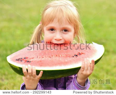 可爱的小女孩在草地上吃西瓜