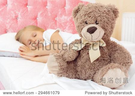 可爱的小女孩和她的泰迪熊睡在床上