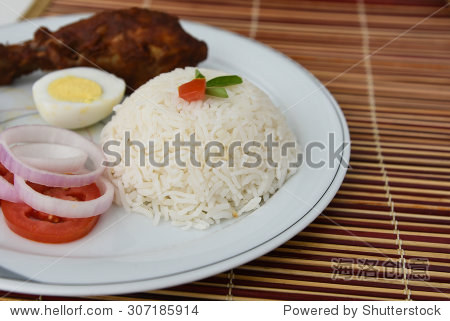 drumsticks egg onion rings and tomato served on a white plate on
