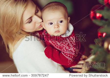 妈妈在白色毛衣金发吻小男孩的孩子红毛衣圣诞树和