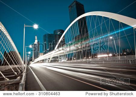 Modern city road arc ironbridge night landscape of car light trails in Tianjing