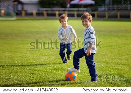 两个可爱的小男孩,户外踢足球,秋天的时间