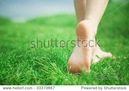 Woman legs walking on green grass