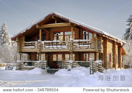 现代的木屋,木制别墅,冬天的木房子,有大窗户,阳台和走廊,白雪覆盖的