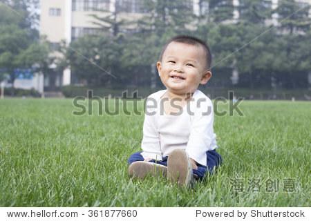 可爱的中国小男孩坐在草地上