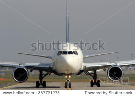 白色的飞机在机场滑行道上出租车