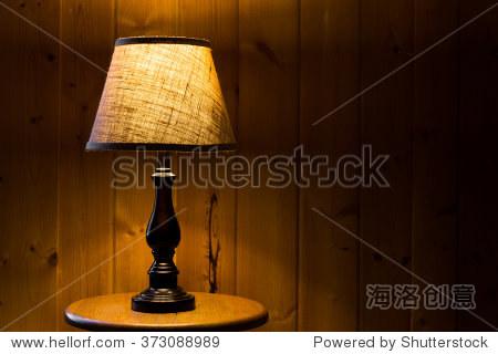 桌面灯与粗麻布帘点燃木纹理背景一个木制的桌子上