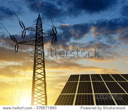 日落时太阳能电池板与电塔.清洁能源的概念.