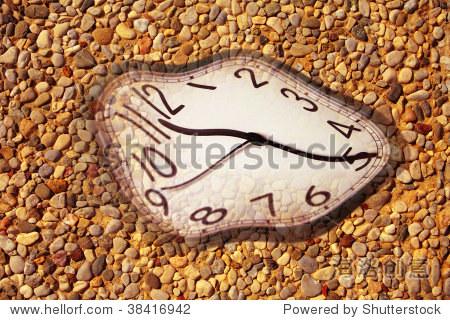 融化的时钟在卵石石头的图片背景