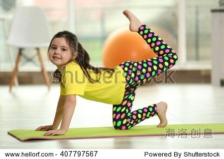 可爱的小女孩在垫室内练习瑜伽姿势