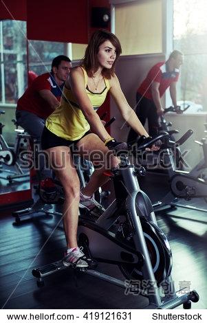 骑自行车的女孩运动在健身房训练。运动人在旋