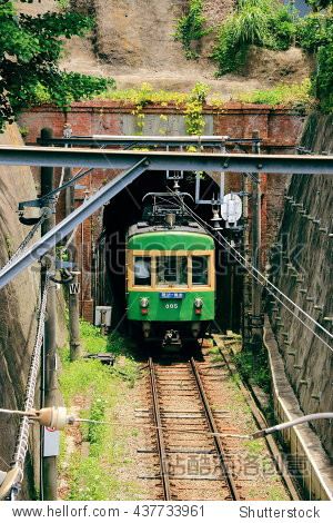 an old-style japanese train (enoden) coming out from a tunnel.