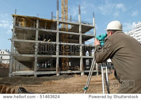 工人测量员测量距离,海拔高度和方向在建筑工地经纬仪