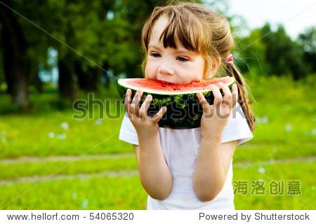 可爱的小女孩在夏天吃西瓜在草地上